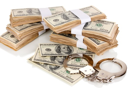 Handcuffs and packs of dollars isolated on white photo