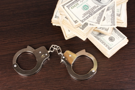 Handcuffs and packs of dollars on wooden table close-up Stock Photo - 15652234