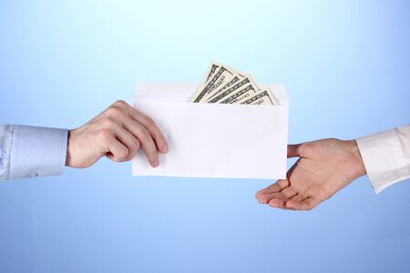man's hand passes the envelope with dollars on blue background Фото со стока