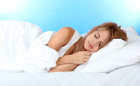 young beautiful woman sleeping on bed on blue background photo