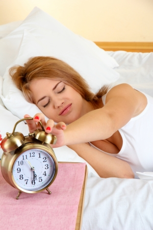 young beautiful woman sleeping on bed with alarm clock in bedroom Stock Photo - 17129703