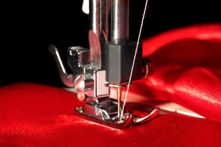 Sewing machine with red cloth closeup photo