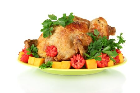 baked whole chicken with vegetables on a green plate isolated on white photo