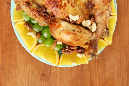 whole roasted chicken with grapes, oranges and spices on blue plate on wooden background close-up photo
