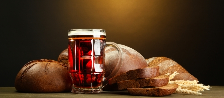 tankard of kvass and rye breads with ears, on wooden table on brown background Stock Photo - 15643672