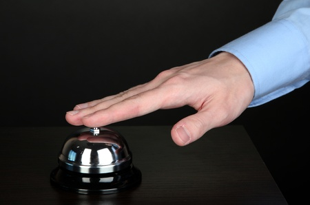 Hand ringing in service bell on wooden table on black background Stock Photo - 15643504