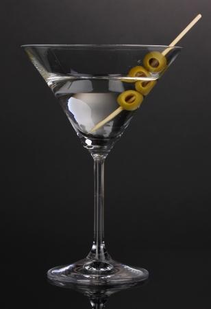 copa de martini: Martini y aceitunas de vidrio sobre fondo gris