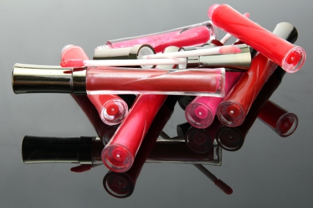 glosses: beautiful lip glosses with rose petals, on grey background