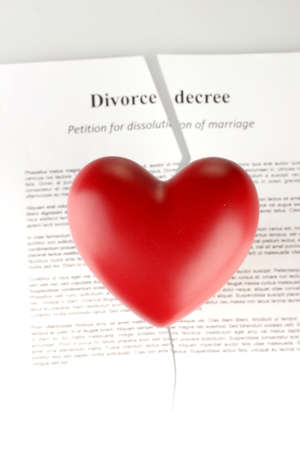 red heart with torn Divorce decree document, on white background close-up photo