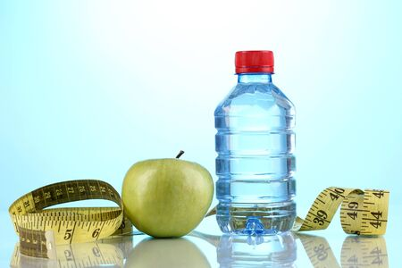 Bottle of water, apple and measuring tape on blue background photo