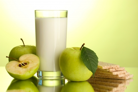 kefir: Glass of kefir, apples and crispbreads, on green background Stock Photo