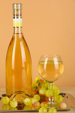 White wine in glass with bottle on salver on beige background photo