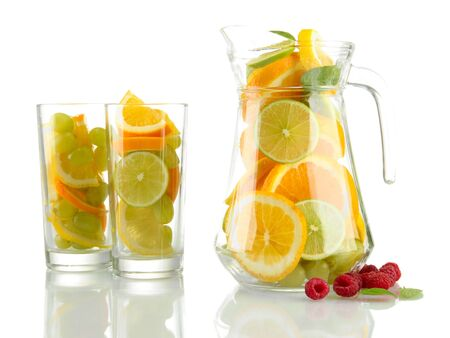transparent jar and glasses with citrus fruits and raspberries, isolated on white photo