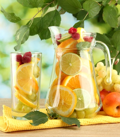 jar and glass with citrus fruits and raspberries, on green background Stock Photo - 15643882