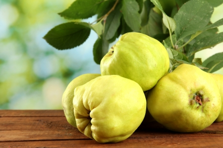 quinces: sweet quinces with leaves, on wooden table, on green background Stock Photo