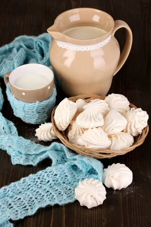 pasteurized: Pitcher and cup of milk with meringues on wooden table close-up Stock Photo