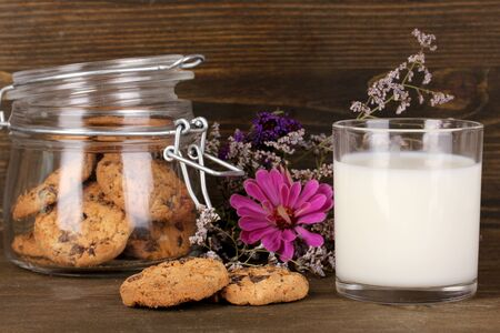 pasteurized: Glass of milk with cookies on wooden table close-up