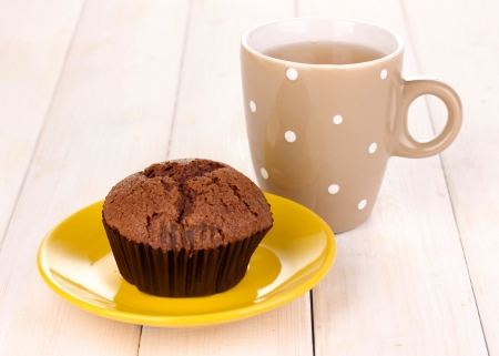 Fresh muffin with tea on wooden background photo