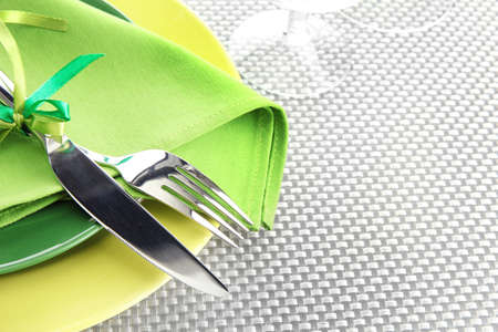 Green empty plates with fork and knife on a grey tablecloth photo