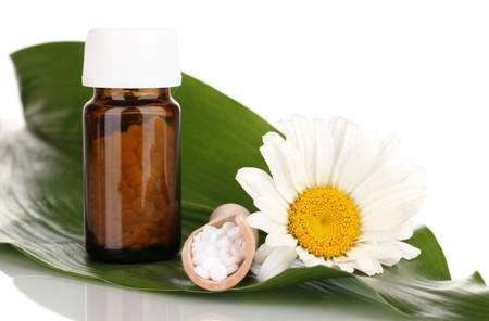 alternative medicine: homeopathic tablets and flower on green leaf isolated on white