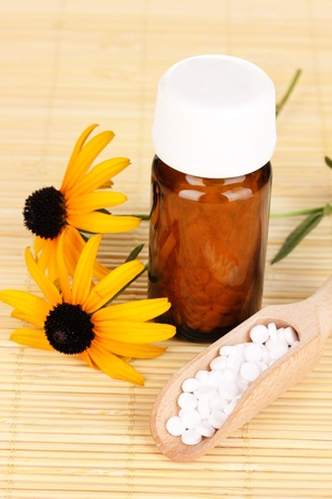 medicine bottle with tablets and flowers on bamboo mat photo