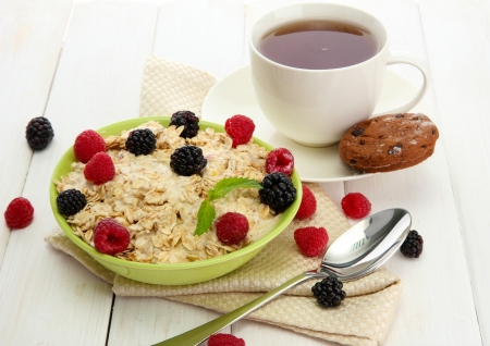 tasty oatmeal with berries and cup of tea, on white wooden table photo