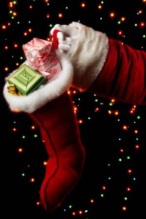 Santa Claus hand holding gifts on bright background Stock Photo - 15688726