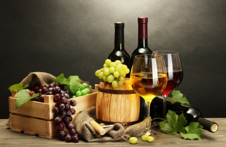 wine  pink: barrel, bottles and glasses of wine and ripe grapes on wooden table on grey background Stock Photo
