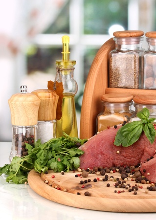 A large piece of pork marinated with herbs, spices and cooking oil on board on white table on window background Stock Photo - 15690101