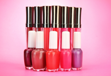 beautiful lip glosses and nail polish bottles, on pink background photo