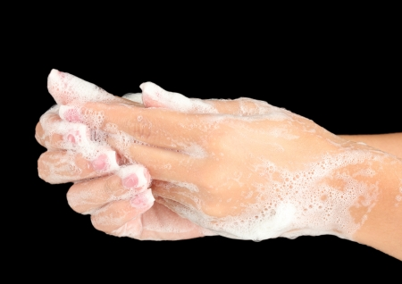 soapsuds: Womans hands in soapsuds, on black background close-up