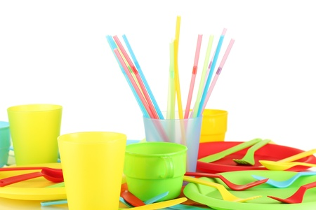 bright plastic disposable tableware on white background close-up photo