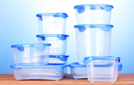 tupperware: Plastic containers for food on wooden table on blue background Stock Photo