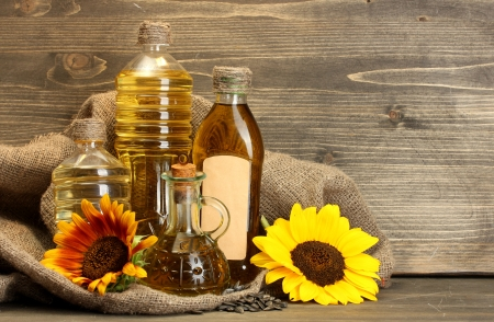 sunflower oil: oil in bottles, sunflowers and seeds, on wooden background