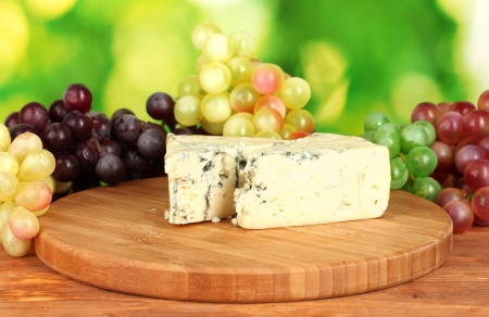veined: Cheese with mold on the cutting board with grapes on bright green background
