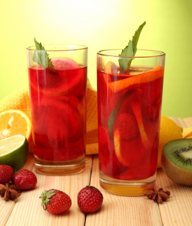 sangria in glasses with fruits, on wooden table, on green background photo
