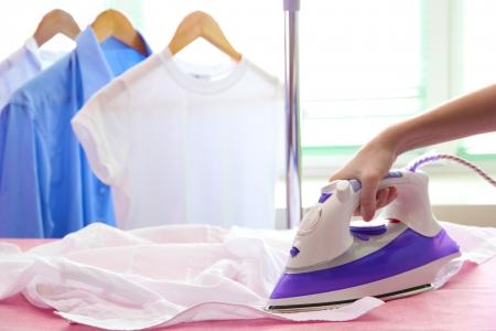 ironing: Woman hand ironing a shirt, on cloth background
