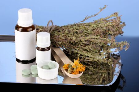 bottles of medicines and herbs on blue background. concept of homeopathy photo