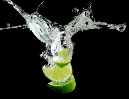 Sliced lime in the water on black background photo