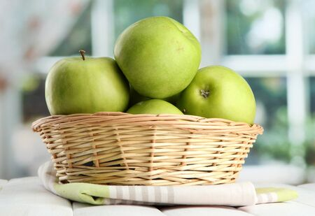 Ripe green apples with leaves in basket, on wooden table, on window background Stock Photo - 15727096