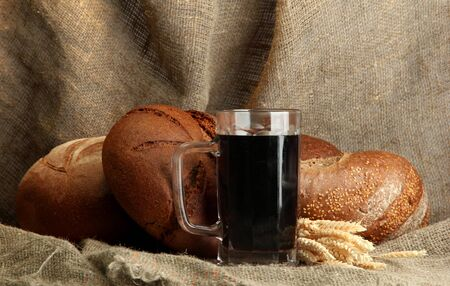 tankard: tankard of kvass and rye breads with ears, on burlap background