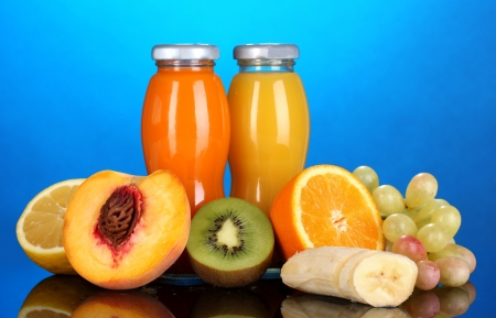 Delicious multifruit juice in a bottle and fruit next to it on blue background photo