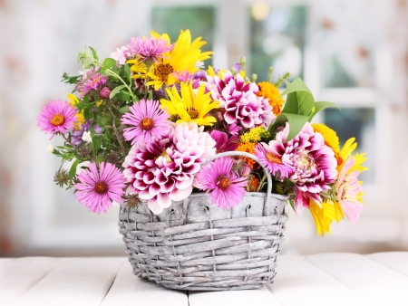 mixed flower bouquet: beautiful bouquet of bright flowers in basket on wooden table Stock Photo
