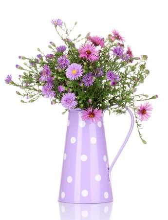 floral arrangement: beautiful bouquet of purple flowers in watering can isolated on white Stock Photo