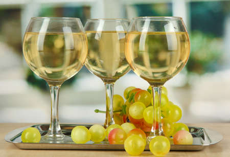 degustation: White wine in glass on salver on window background