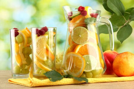 jar and glasses with citrus fruits and raspberries, on green background Stock Photo - 15729441