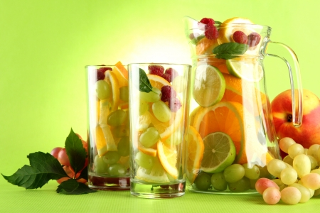 jar and glasses with citrus fruits and raspberries, on green background Stock Photo - 15726071