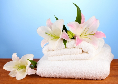 stack of towels with pink lily on blue background photo