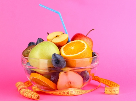 Glass bowl with fruit for diet and measuring tape on pink background Stock Photo - 15726503