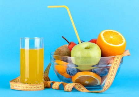 Glass bowl with fruit for diet and juice on blue background Stock Photo - 15729162